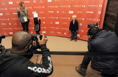 Photographers kneel down to shoot Finn Donoghue, 4, a cast member in