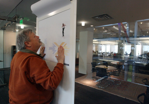 Steve Griffin  |  The Salt Lake Tribune   The University of Utah is hosting a month-long Olympic Experience Exhibition in the Marriott Library in Salt Lake City, Utah. Here archivist, Roy Webb, hangs a poster for display Tuesday, January 31, 2012.