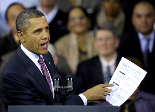 President Barack Obama holds up a proposed mortgage application form as he speaks at the James Lee Community Center in Falls Church, Va., Wednesday, Feb. 1, 2012. Obama outlined a proposal he proposed in his State of the Union address to allow homeowners with privately held mortgages to take advantage of record low rates, for an annual savings of about $3,000 for the average borrower.  (AP Photo/Cliff Owen)