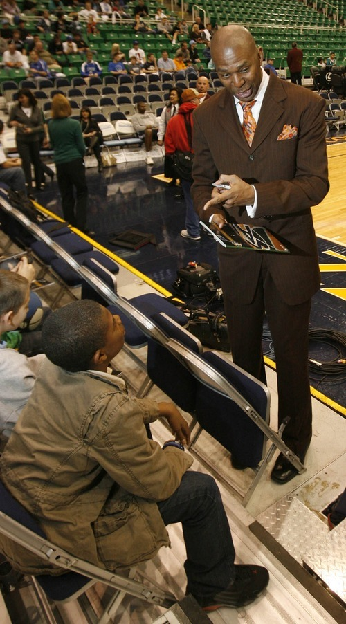 Paul Fraughton | The Salt Lake Tribune. Thurl Bailey chats with a young fan as he signs an autograph before the game. The Utah Jazz played Portland at Energy Solutions Arena.  Monday, January 30, 2012