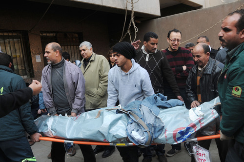 Mourners carry the body of a victim of clashes at a soccer stadium outside a morgue in Cairo, Egypt, Thursday, Feb. 2, 2012. Scores of Egyptian soccer fans were crushed to death Wednesday, Feb. 1, 2012, while others were fatally stabbed or suffocated after being trapped in a long narrow corridor trying to flee rival fans armed with knives, clubs and stones, in the country's worst ever soccer violence that killed at least 74 people, witnesses and health officials said Thursday. (AP Photo/  Mohammed Asad)