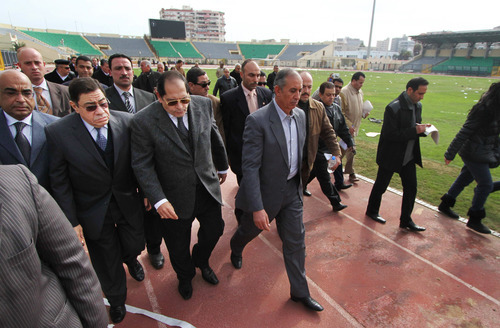 Prosecutor-General Mahmoud Abdel-Meguid, second left, tours a stadium with other officials the morning after deadly clashes occurred in Port Said, Egypt, Thursday, Feb. 2, 2012. Scores of Egyptian soccer fans were crushed to death while others were fatally stabbed or suffocated after being trapped in a long narrow corridor trying to flee rival fans armed with knives, clubs and stones, in the country's worst ever soccer violence that killed at least 74 people, witnesses and health officials said Thursday. Head of sports committee in parliament, said that the parliament holds the interior minister responsibility for the violence. He demanded ouster of the Prosecutor-General Mahmoud Abdel-Meguid to guarantee