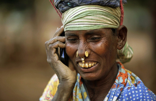 An Indian daily wage laborer talks on a mobile phone, at a construction site in Bhubaneshwar, India, Thursday, Feb. 2, 2012. India's top court ordered the government on Thursday to cancel 122 licenses granted to companies during an irregular sale of cellphone spectrum that has been branded one of the largest scandals in the country's history.  (AP Photo/Biswaranjan Rout)
