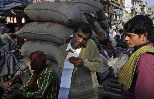 A vendor takes an order from a customer on his mobile phone at a wholesale market, in New Delhi, India, Thursday, Feb. 2, 2012. India's top court ordered the government on Thursday to cancel 122 cellphone licenses granted to companies during an irregular sale of spectrum that has been branded one of the largest scandals in India's history. (AP Photo/Manish Swarup)