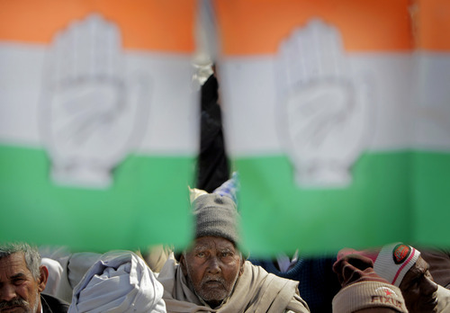 Spectators sit under a festoon of flags of the Congress Party at an election rally in Meerut, India, Thursday, Feb. 2, 2012.  India's biggest state, Uttar Pradesh, will be choosing its state assembly in elections testing the popularity of the national government's ruling Congress party. The elections starting next week are being viewed as a make or break moment for Congress party leader Rahul Gandhi. (AP Photo/Gurinder Osan)
