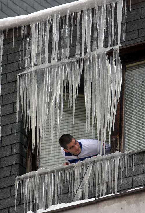 A man views icicles on a window in Uzice 200 kilometers (125 miles) southwest of Belgrade, Serbia, Thursday, Feb. 2, 2012. At least 11,000 villagers have been trapped by heavy snow and blizzards in Serbia's mountains, authorities announced Thursday, as the death toll from Eastern Europe's weeklong deep freeze rose to 122. .(AP Photo)