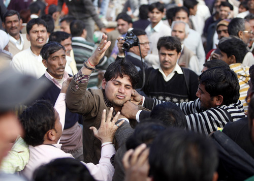 Media personnel beat up a spectator who was allegedly stealing at an election rally addressed by Congress Party leader Rahul Gandhi in Meerut, India, Thursday, Feb. 2, 2012. India's biggest state, Uttar Pradesh, will be choosing its state assembly in elections testing the popularity of the national government's ruling Congress Party. (AP Photo/Gurinder Osan)