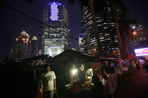 Office workers have dinner at food stalls at the main business district in Jakarta, Indonesia, Thursday, Feb. 2, 2012. (AP Photo/Dita Alangkara)