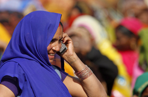 An Indian woman talks on her mobile phone at an election rally in Faizabad, India, Thursday, Feb. 2, 2012. India's top court ordered the government on Thursday to cancel 122 cellphone licenses granted to companies during an irregular sale of spectrum that has been branded one of the largest scandals in India's history. (AP Photo/Rajesh Kumar Singh)