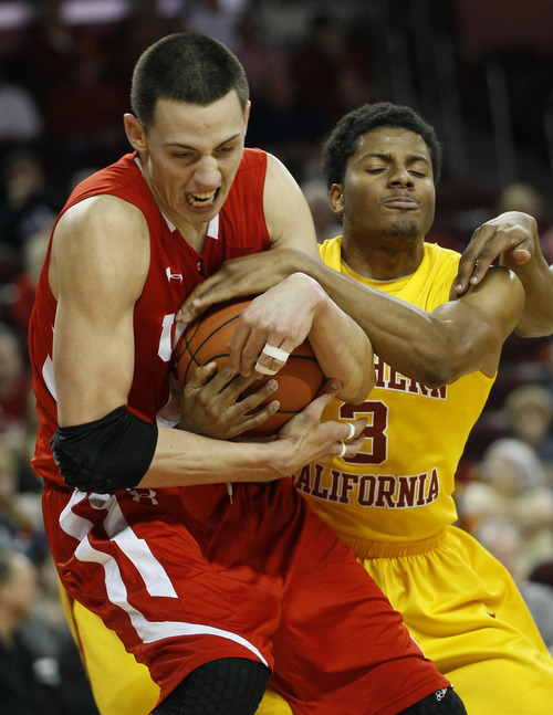 Utah's Jason Washburn, left, and USC's Alexis Moore (3) battle for the ball in the first half of an NCAA college basketball game in Los Angeles, Saturday, Jan. 28, 2012. (AP Photo/Lori Shepler)