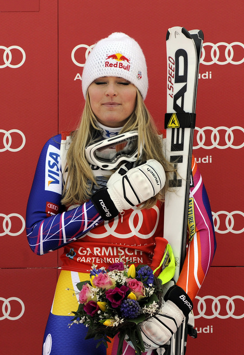 Lindsey Vonn, of the United States, listens to the national anthem during the podium ceremony after winning an alpine ski, women's World Cup downhill, in Garmisch-Partenkirchen, Germany, Saturday, Feb. 4, 2012. Vonn captured her 50th World Cup career victory by winning the downhill on the demanding Kandahar course on Saturday. The American is third on the all-time list, behind Annemarie Moser-Proell of Austria with 62 victories and Vreni Schneider of Switzerland with 55. Vonn now has 25 downhill wins, second behind Moser-Proell's 36. (AP Photo/Giovanni Auletta)