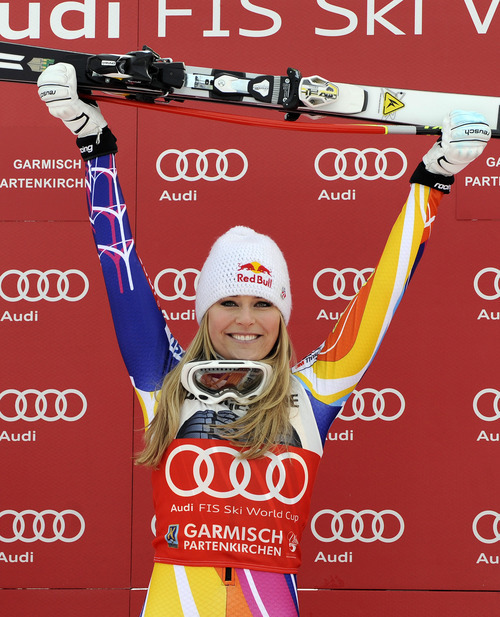 Lindsey Vonn, of the United States, celebrates on the podium after winning an alpine ski, women's World Cup downhill, in Garmisch-Partenkirchen, Germany, Saturday, Feb. 4, 2012. Vonn captured her 50th World Cup career victory by winning the downhill on the demanding Kandahar course on Saturday. The American is third on the all-time list, behind Annemarie Moser-Proell of Austria with 62 victories and Vreni Schneider of Switzerland with 55. Vonn now has 25 downhill wins, second behind Moser-Proell's 36. (AP Photo/Giovanni Auletta)