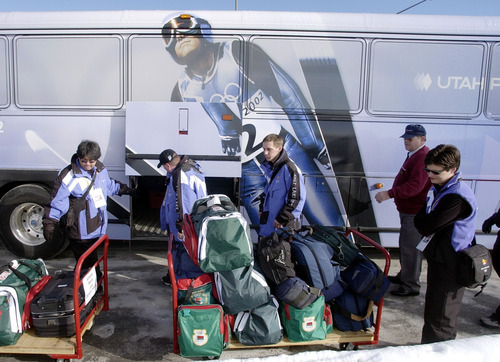 Tribune file photo Volunteers load bags for reporters from Belarus at the Salt Lake City International Airport at the opening of the 2002 Games.