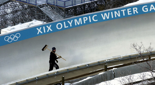 Tribune file photo A maintainence worker walks up the bobsled track at the end of a day of Olympic competition in 2002.