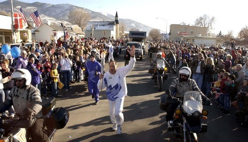 The Olympic Torch Relay arrives on Main Street in Manti for the 2002 Salt Lake Olympics.