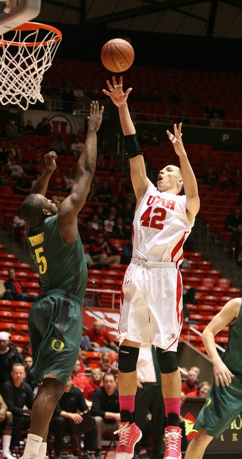 Paul Fraughton | The Salt Lake Tribune. Utah's Jason Washburn shoots over Oregon's Olu Ashaolu. Utah played Oregon in THe Huntsman Center.  Thursday, February 2, 2012