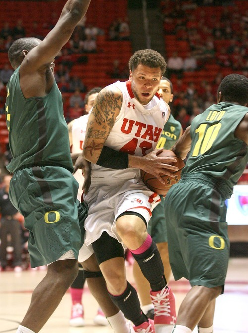 Paul Fraughton | The Salt Lake Tribune. Cedric Martin, going to the basket,  is sandwiched  between Oregon's Olu Ashaolu  and Jonathan Loyd.  Oregon defeated Utah 68 to 79 in The Huntsman Center.  Thursday, February 2, 2012