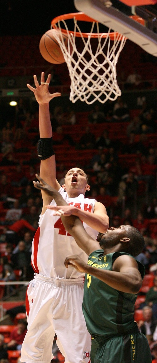 Paul Fraughton | The Salt Lake Tribune. Utah's Jason Washburn misses his shot as Oregon's Olu Ashaolu defends.Oregon defeated Utah 68 to 79 in The Huntsman Center.  Thursday, February 2, 2012