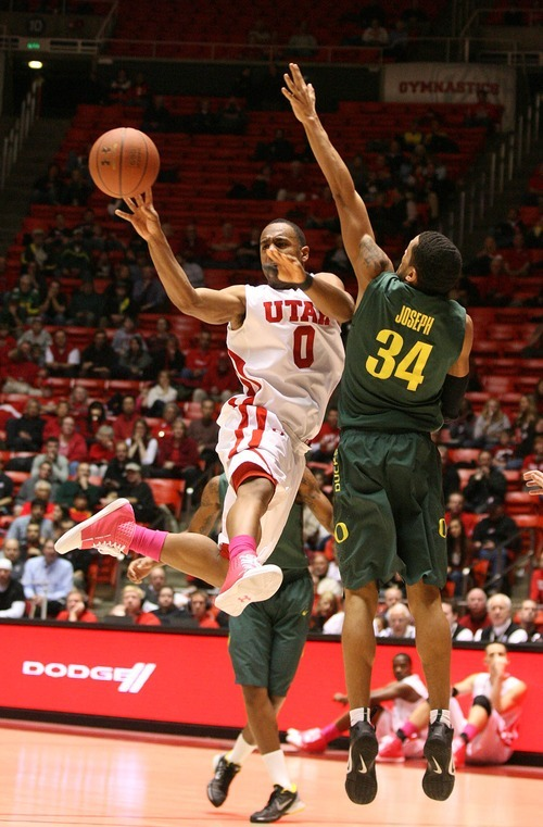 Paul Fraughton | The Salt Lake Tribune. Utah's Chris Hines passes the ball as he goes up against Oregon's Devoe Joseph.  Oregon defeated Utah 68 to 79 in The Huntsman Center.  Thursday, February 2, 2012