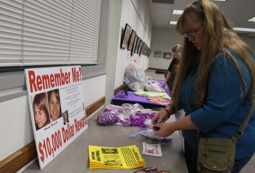 Rick Egan  | The Salt Lake Tribune   Kiirsi Helliwell arranges purple ribbons and bracelets on a table at the Hunter Library in West Valley City on Monday. Friends and family of missing West Valley City woman Susan Cox Powell gathered donations for the Christmas Box House.