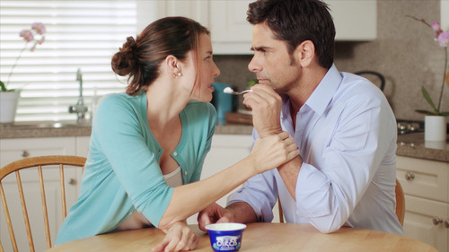 This advertisement  provided by Dannon Co,. shows a scene from the Dannon Oikos Greek Yogurt Super Bowl commercial, starring Jessica Blackmore and John Stamos. The Dannon Oikos advertisement will run during the third quarter of Super Bowl XLVI, Sunday, Feb 5, 2012. (AP Photo/Dannon Co.)