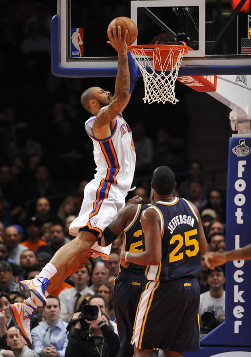 New York Knicks' Tyson Chandler (6) dunks over Utah Jazz's Paul Millsap and Al Jefferson (25) during the first half of an NBA basketball game Monday, Feb. 6, 2012, in New York. (AP Photo/Kathy Kmonicek)