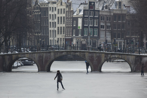 The first daredevils on skates test the ice on the frozen Keizersgracht canal in Amsterdam, Netherlands, Sunday Feb. 5, 2012, as temperatures dropped below -10 degrees Celsius (14 degrees Fahrenheit) overnight and remained at -5 degrees Celsius (23 degrees Fahrenheit) during the daytime. (AP Photo/Peter Dejong)