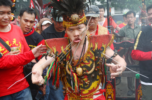 A worshipper pierces his cheeks with metal skewers during Cap Go Meh festival that marks the end of Lunar New Year celebrations in Jakarta, Indonesia, Monday, Feb. 6, 2012. (AP Photo/Tatan Syuflana)