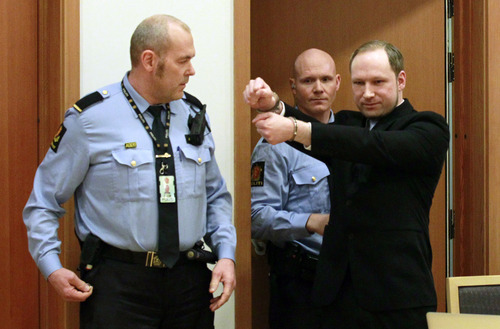 Anders Behring Breivik, right, a right-wing extremist who confessed to a bombing and mass shooting that killed 77 people on July 22, 2011, gestures as he arrives for a detention hearing at a court in Oslo, Norway, Monday, Feb. 6, 2012. About 100 survivors and relatives of the victims of the July 22 massacre attended the hearing in Oslo's district court - expected to decide to keep Breivik in jail until his trial begins in April. (AP Photo/Heiko Junge, Scanpix Norway) NORWAY OUT