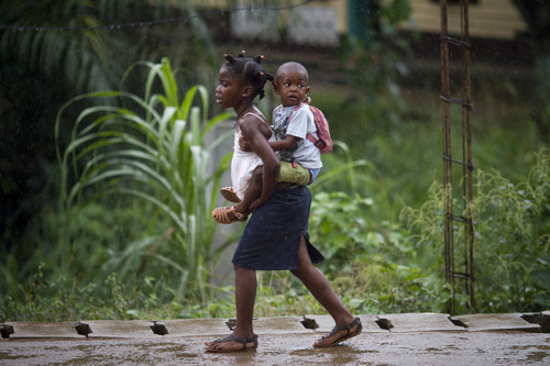 A girl carries a child as they walk back from school during a rain shower in Bata, Equatorial Guinea, Monday, Feb. 6, 2012. (AP Photo/Ariel Schalit)