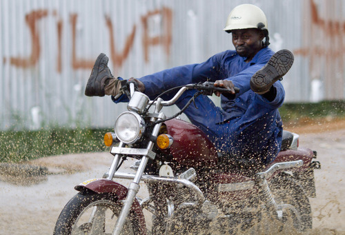 A motorcyclist drives through a road which flooded after rain showers in Bata, Equatorial Guinea, Monday, Feb. 6, 2012. (AP Photo/Ariel Schalit)