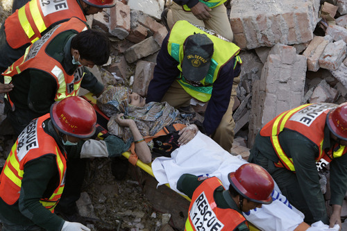 Pakistani rescue workers carry a woman who was recovered from the debris of a collapsed building in Lahore, Pakistan, Monday, Feb. 6, 2012. A three-story factory illegally set up in a residential area of Lahore collapsed Monday after several gas cylinders inside exploded, killing at least two people and trapping over 40 others in the rubble, officials said. (AP Photo/K.M. Chaudary)
