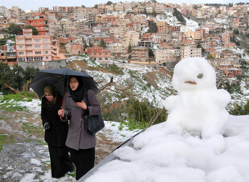 Two women walk past a snowman in Algiers, Algeria, Monday, Feb. 6, 2012. Snow made a rare appearance in Algiers, the capital city of Algeria. Meteorology reports suggest that the last time Algiers saw this amount of snow was at least seven years ago in 2005. (AP Photo/Ouahab Hebbat)