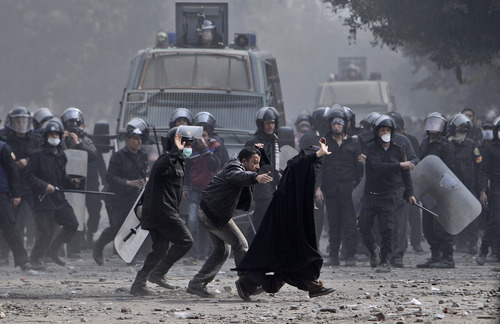 An Egyptian woman runs away after being caught between riot police and stone-throwers during clashes near the Interior Ministry in Cairo, Egypt, Monday, Feb. 6, 2012.  (AP Photo/Muhammed Muheisen)