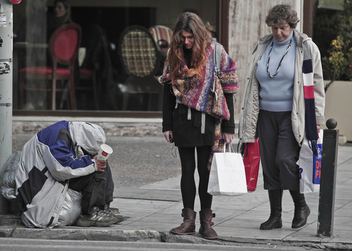 Pedestrians pass by a beggar off Athens' main Syntagma Square, on Friday, Feb. 3, 2012. Unions and employers' associations in Greece on Friday rejected private-sector wage cuts, as demanded by the country's international bailout lenders if Athens is to receive a crucial, second rescue package. The impasse appeared to be holding up final negotiations for massive new debt agreements _ a eurozone finance ministers' meeting, which had been expected for Monday to back the new proposals, was postponed to later in the week.  (AP Photo/Dimitri Messinis)