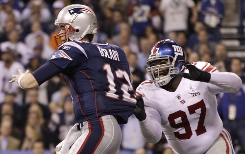 New York Giants defensive tackle Linval Joseph (97) grabs New England Patriots quarterback Tom Brady (12) during the second half of the NFL Super Bowl XLVI football game, Sunday, Feb. 5, 2012, in Indianapolis. (AP Photo/Matt Slocum)