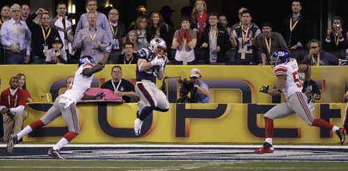 New England Patriots running back Danny Woodhead (39) scores a touchdown as New York Giants Kenny Phillips (21) and Michael Boley (59) defend during the first half of their NFL Super Bowl XLVI football game, Sunday, Feb. 5, 2012, in Indianapolis. (AP Photo/David Duprey)