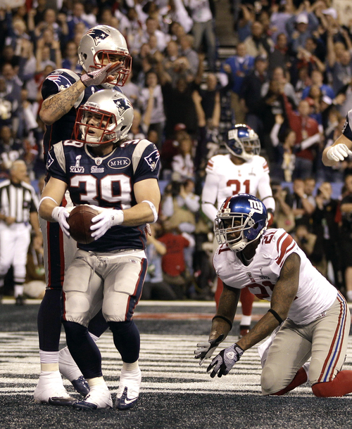 New England Patriots running back Danny Woodhead (39) celebrates with Aaron Hernandez, rear, after scoring a touchdown as New York Giants safety Kenny Phillips (21) looks on during the first half of the NFL Super Bowl XLVI football game, Sunday, Feb. 5, 2012, in Indianapolis. (AP Photo/Matt Slocum)