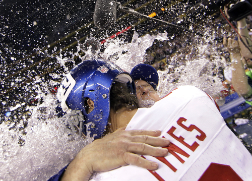 New York Giants kicker Lawrence Tynes hugs head coach Tom Coughlin as they get doused with liquid at the end of the NFL Super Bowl XLVI football game against the New England Patriots, Sunday, Feb. 5, 2012, in Indianapolis. The Giants won 21-17. (AP Photo/David J. Phillip)