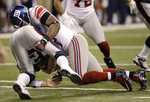 New York Giants defensive end Justin Tuck, top, sacks New England Patriots quarterback Tom Brady during the second half of the NFL Super Bowl XLVI football game Sunday, Feb. 5, 2012, in Indianapolis. (AP Photo/David J. Phillip)