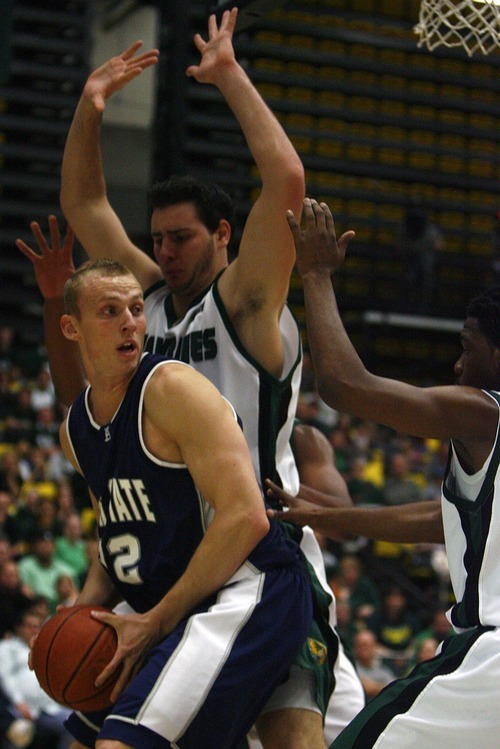 Djamila Grossman  |  The Salt Lake Tribune  Utah State University's Brady Jardine, 22, looks on to pass the ball as Utah Valley University's Rory Fannon, 42, and Isiah Williams, 2, block him, during the first half of a game at UVU, Saturday, Dec. 18, 2010.