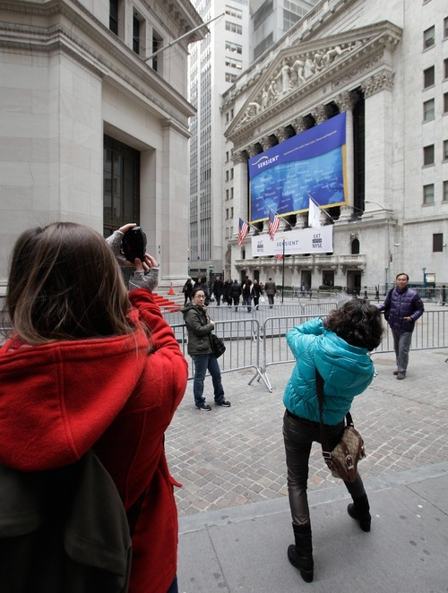 Richard Drew  |  The Associated Press People take pictures in front of the New York Stock Exchange, Thursday. For the NYSE, once a crossroads of American capitalism and now little more than a TV backdrop, winning Facebook would be a chance to regain some prestige.