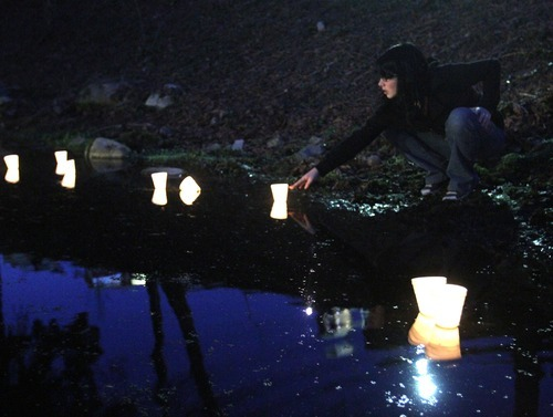 Rick Egan  | The Salt Lake Tribune   Taylor, Puyallup, Washington, drops a candle into McKinley Pond during a vigil  at McKinley Park in Tacoma, Monday, February 6, 2012.  Between 300 and 400 people attended the vigil.
