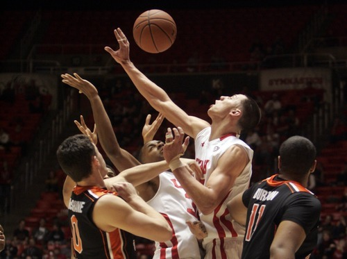 Kim Raff |The Salt Lake Tribune University of Utah players (left) Anthony Odunsi and Jason Washburn battle for a rebound with Oregon State players (left) Kevin McShane and Joe Burton during the second half at the Huntsman Center in Salt Lake City, Utah on February 4, 2012. Utah went on the lose the game 58-76.