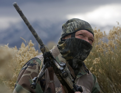 Al Hartmann  |  The Salt Lake Tribune Bill Keebler waits in camoflague in the brush with a high view of an area and waits for coyote or uses one of his coyote calls to lure them in. His guide and outfitter service is headquartered in Tooele County.