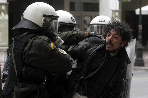 Riot police detain a protester during clashes in Athens, Friday, Feb. 10, 2012. Thousands took to the streets of Athens as unions launched a two-day general strike against planned austerity measures on Friday, a day after Greece's crucial international bailout was put in limbo by its partners in the 17-nation eurozone.  (AP Photo/Petros Giannakouris)