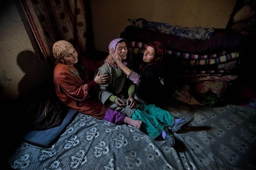 Unidentified women comfort a wailing relative of Gul Mohammad Dar, a pro-India party worker and a rural body head, during his funeral procession in Hawoormisshipora village, some 65 Kilometers (40 miles) south of Srinagar, India, Friday, Feb. 10, 2012. Police in Indian Kashmir say unidentified gunmen shot dead a political worker and a rural body head of pro-Indian party and wounded another late Thursday night. At least 698 politicians including leaders and workers were killed in Indian-controlled Kashmir since 1990, according to a 2011 government statistic. (AP Photo/Dar Yasin)