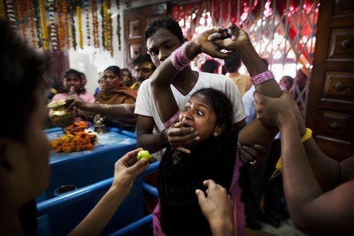 A Tamil Hindu priest pushes lemons into a female worshipper's mouth as she is in trance during a ritual for the festival of Thaipusam in a temple in New Delhi, India, Friday, Feb. 10, 2012. Thaipusam, an annual festival that celebrates the victory of good over evil, marks the day when Goddess Parvati presented a weapon to Murugan, her son with Hindu God Shiva, to vanquish a demon army. (AP Photo/Kevin Frayer)