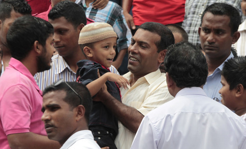 Maldives' former President Mohamed Nasheed, center, lifts a child as he walks out from a Mosque following prayers with his supporters in Male, Maldives, Friday, Feb. 10, 2012. (AP Photo/Eranga Jayawardena)