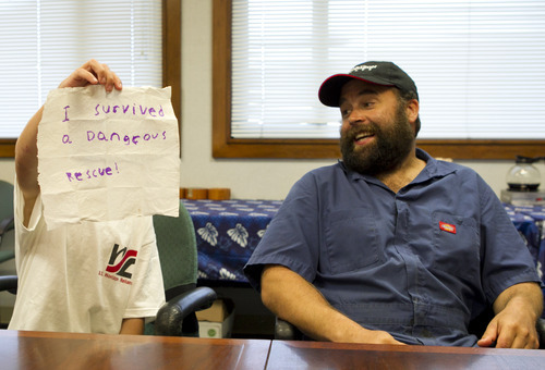 Bradley James, right, reacts to a note his nine-year-old West James wrote while in the offices of Horizon Shipping after they were rescued from their sinking sail boat by a cargo ship, Thursday, Feb. 9, 2012 in Honolulu.  The Canadian family was attempting their first voyage across the Pacific in a sailboat when rough seas damaged their boat hundreds of miles from land.   (AP Photo/Marco Garcia)